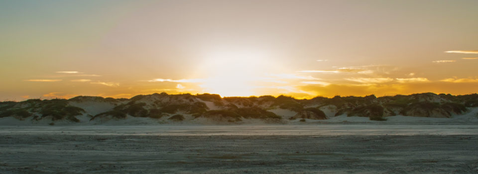 Texas Sun setting over Sand Dunes on Padre Island Beach